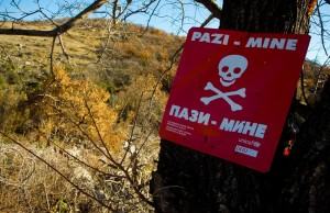 """A sign """"Beware of mines"""" on the tree beside road in outskirts of southern-eastern Bosnian town of St"""